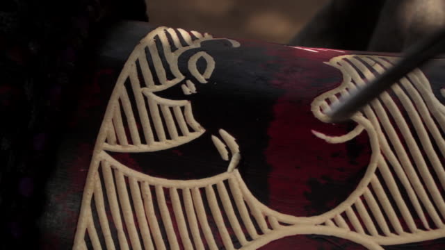 Close shot of a person carving patterns onto the side of a wooden drum.