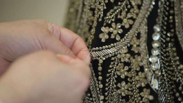 Close shot of a person sewing beads onto a garment.