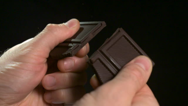 vidéos et rushes de close shot of a person snapping apart pieces of dark chocolate. - chocolat