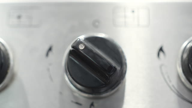 close shot of a person turning a dial on a cooker. - cooker stock videos and b-roll footage
