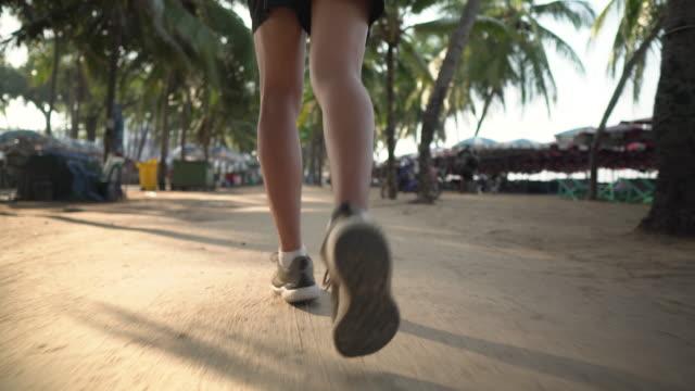 vídeos y material grabado en eventos de stock de tiro cercano de un corredor corriendo en la playa - miembro humano