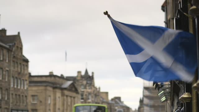 Close shot of a Scottish flag flying on a flagpole on a street in Edinburgh.
