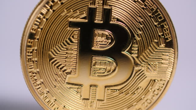close shot of a single bitcoin slowly revolving. - bitcoin stock videos and b-roll footage