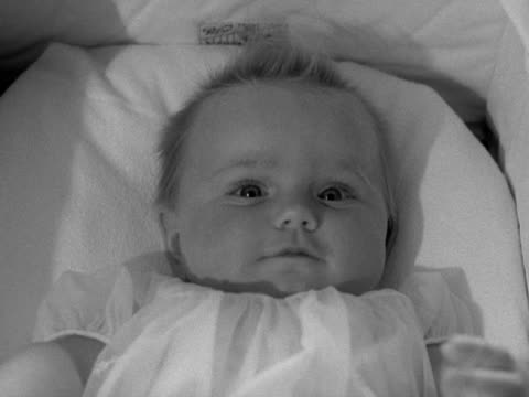 close shot of a smiling baby in a carry cot - dondolarsi video stock e b–roll