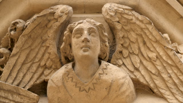 close shot of a stone angel decorating the exterior of a building at trinity college, cambridge. - trinity college cambridge university stock videos & royalty-free footage