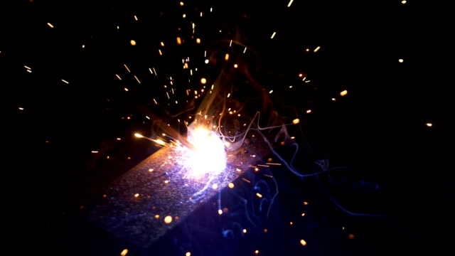 Close shot of a welder welding pieces in slow motion