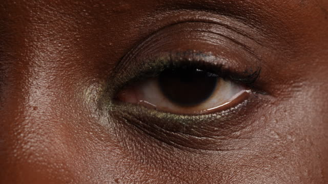 close shot of a woman's left eye. - brown eyes stock videos & royalty-free footage