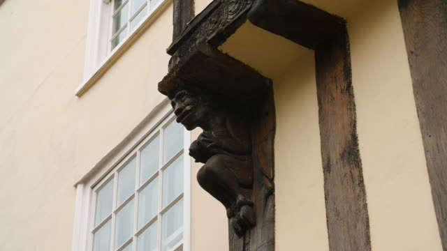 close shot of a wooden gargoyle decorating the exterior of a house in canterbury. - カンタベリー点の映像素材/bロール