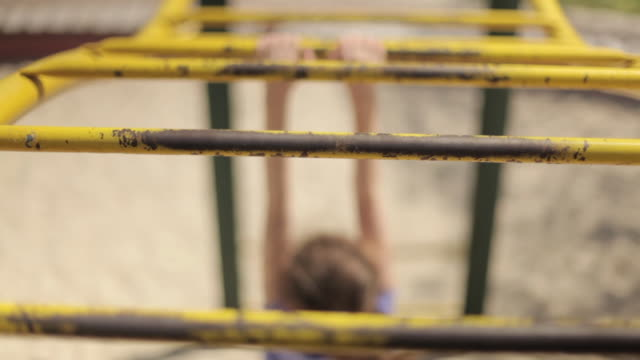 close shot of a young girl moving along a climbing frame. - ジャングルジム点の映像素材/bロール