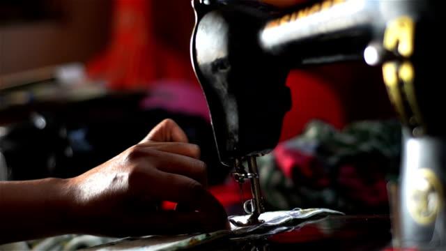 Close shot of adjusting thread in a sewing machine.