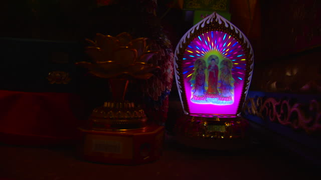 Close shot of an alarm clock with an illuminated buddhist image.