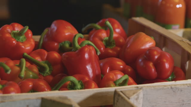 close shot of boxes of red peppers being placed on a table. - pepper vegetable stock videos & royalty-free footage