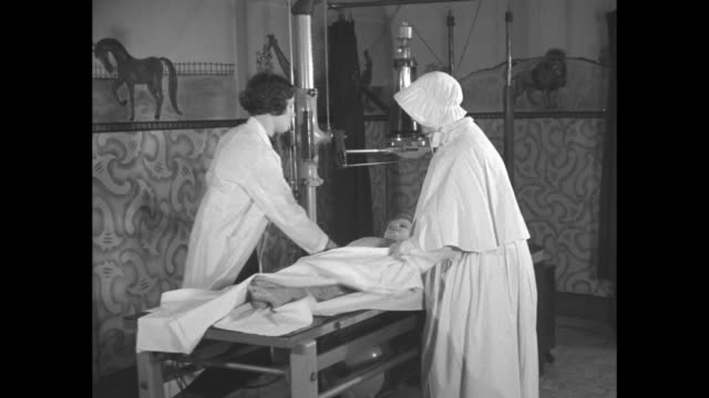Close shot of Catholic nun working in hospital / nun and nurse standing on either side of boy on table they cover him with blanket and move lens of...