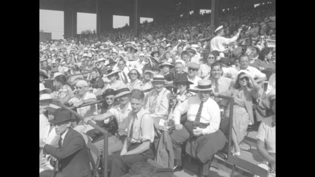 Close shot of celebrity in baseball uniform standing on playing field posing for photo opportunity / comedian Joe E Brown sitting in stands...