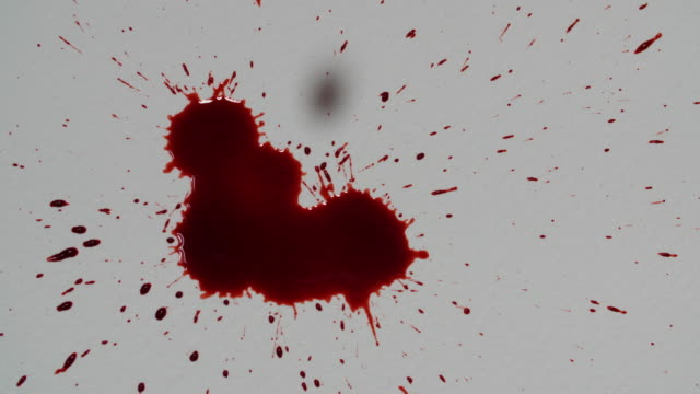 Close shot of fake blood being dropped onto a piece of white paper.