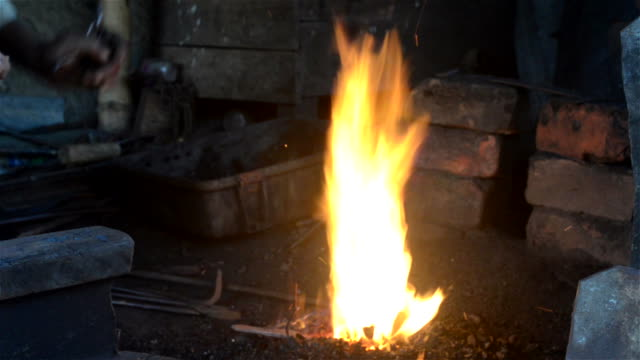 close shot of fire in indian blacksmith workshop. - human limb stock videos & royalty-free footage