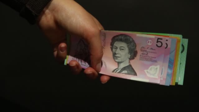 Close shot of hands counting Australian dollar banknotes of various denominations arranged for video in Sydney Australia on Thursday July 24 Close...