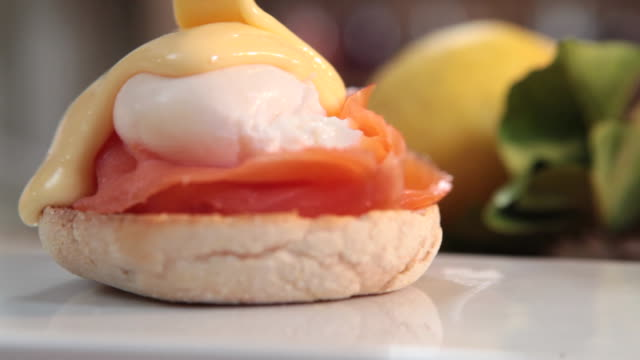 close shot of hollandaise sauce being poured over two portions of eggs benedict. - hollandaise sauce stock videos and b-roll footage