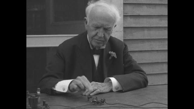 close shot of inventor thomas edison sitting outdoors at table operating telegraph key / note exact month/day not known - telegraph machine stock videos & royalty-free footage