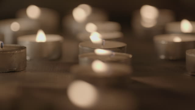 close shot of lit tea lights. - candle stock videos and b-roll footage