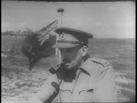 close shot of major general simmons on a speedboat british flag behind him / indian troops with howitzer guns / close up of loading gun / panning... - major military rank stock videos and b-roll footage
