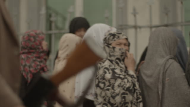close shot of man carrying weapon rack focus to women waiting in line - kabul stock videos & royalty-free footage