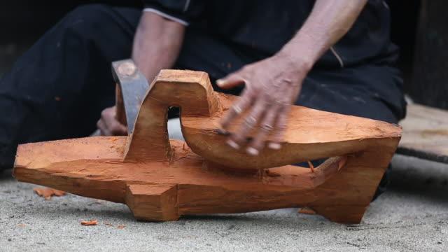 vidéos et rushes de close shot of man's hands using an adze (or axe) on a wood carving, handheld - sculpture production artistique