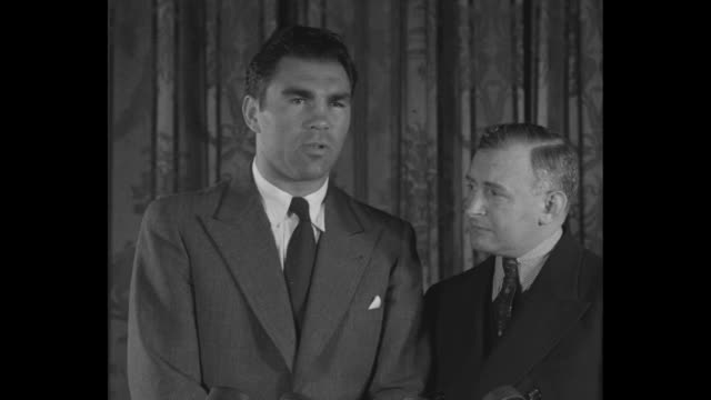 Close shot of Max Schmeling / shot of Schmeling and manager Joe Jacobs as Schmeling speaks about opponent James J Braddock's cancellation of their...