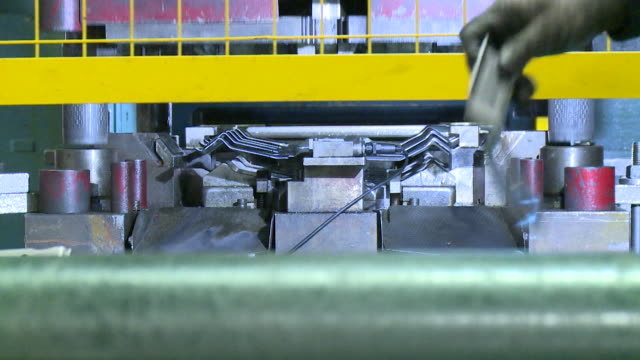 close shot of metal components being pressed into shape in a factory - metal clip stock videos and b-roll footage