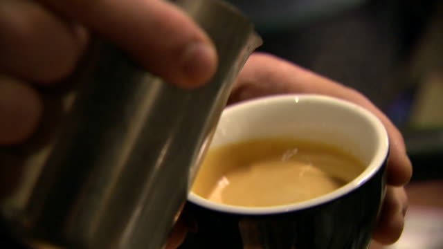 close shot of milk being poured into coffee to create heart shapes - caffeine molecule stock videos & royalty-free footage