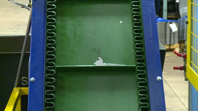 close shot of small metal components travelling on a conveyor belt in a factory - metal clip stock videos and b-roll footage