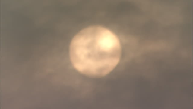 Close shot of sun coloured orange by air pollution and zoom back to smoke belching from smokestack