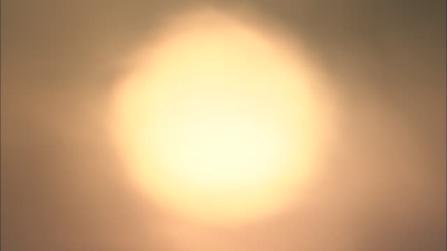 stockvideo's en b-roll-footage met close shot of sun coloured orange by air pollution - vervormd beeld