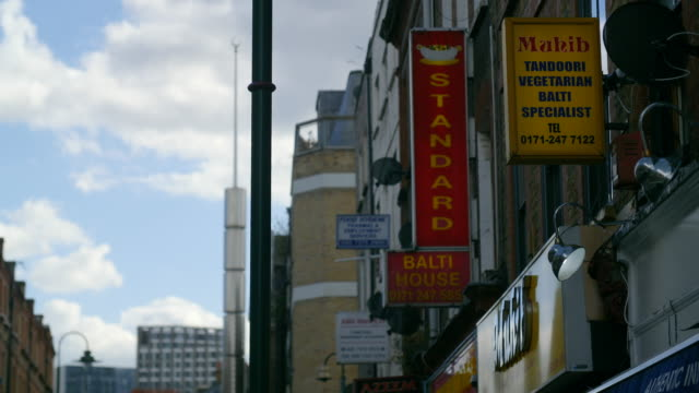 close shot of the signs curry restaurants with the brick lane jamme masjid in background - east london stock videos and b-roll footage