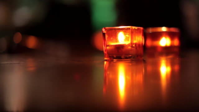 close shot of two tea lights burning in glass containers. - orange colour stock videos & royalty-free footage
