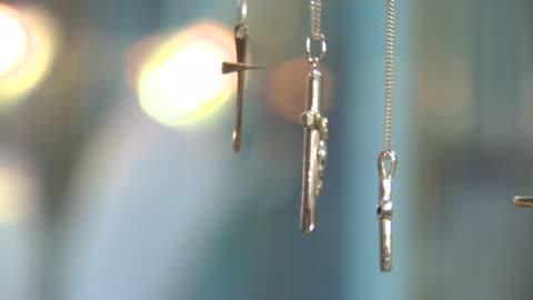 close shot of various cross and crucifix necklaces revolving on a display stand. - kors religiös symbol bildbanksvideor och videomaterial från bakom kulisserna