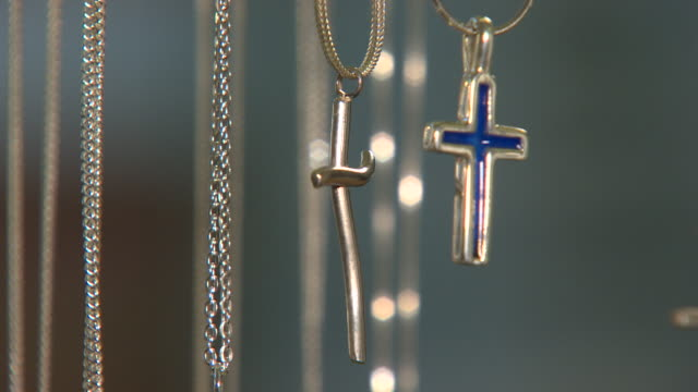 close shot of various silver cross necklaces revolving on a display stand. - halskette stock-videos und b-roll-filmmaterial