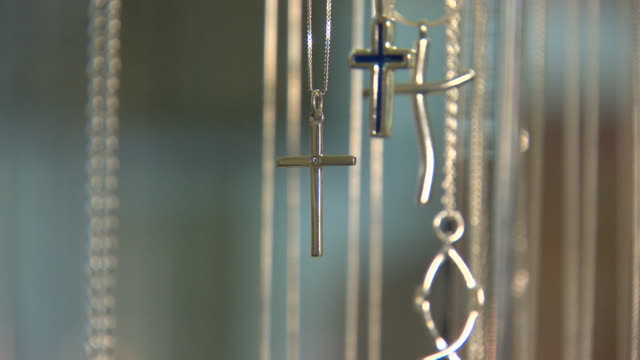 close shot of various silver cross necklaces revolving on a display stand. - chain stock videos & royalty-free footage