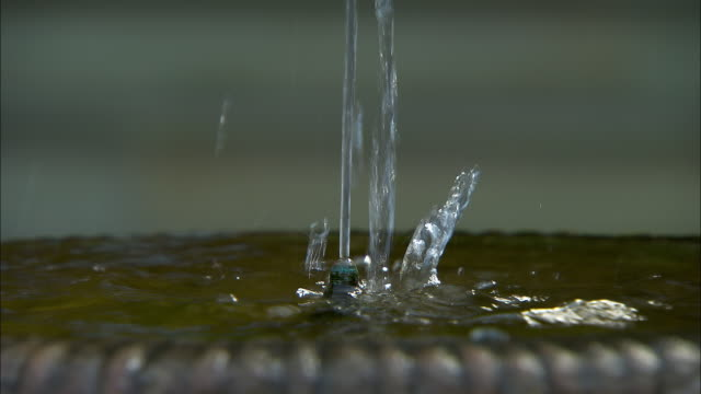 Close shot of water flowing from a water fountain.