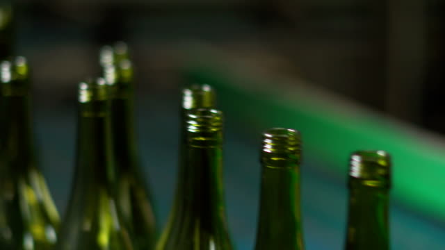 close shot of wine bottles in bottling factory - bottling plant stock videos and b-roll footage