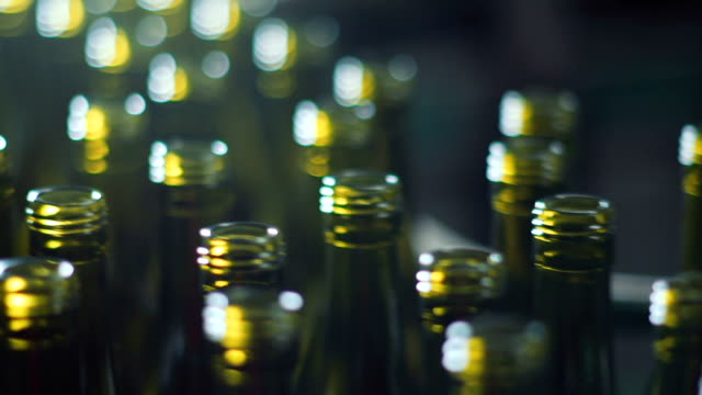 close shot of wine bottles in bottling factory - bottling plant stock videos & royalty-free footage