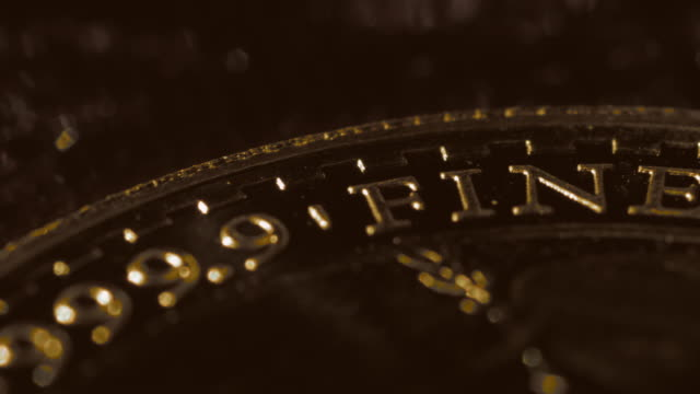 close shot on a gold coin as it slowly revolves. - coin stock videos & royalty-free footage