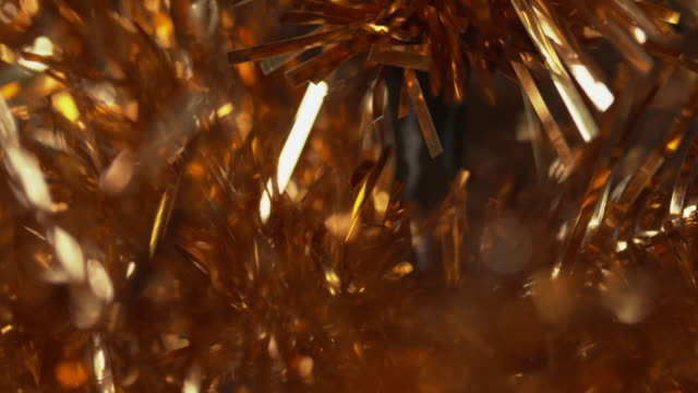 close shot on a gold tinsel christmas tree. - tinsel stock videos & royalty-free footage