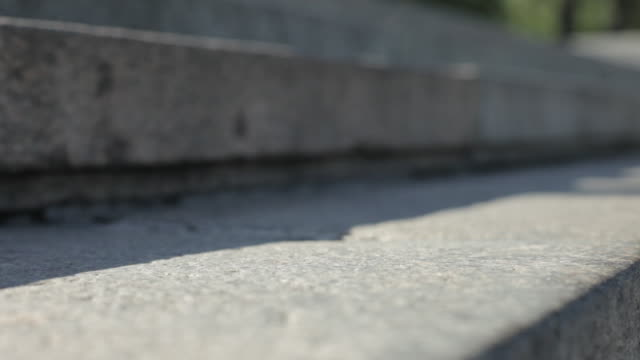 Close shot on a person walking down a flight of stone steps.