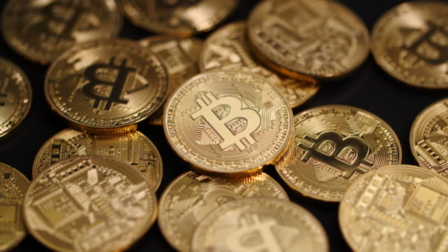 vídeos de stock, filmes e b-roll de close shot on a pile of bitcoins as they slowly revolve. - blockchain