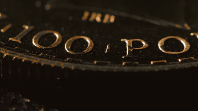 Close shot on the words stamped onto the edge of a gold coin.