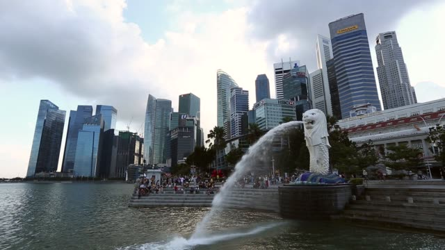 Close shot water spouts from the mouth of a Merlion statue in Singapore on Thursday Feb 18 Visitors take photographs at Merlion Park as buildings in...