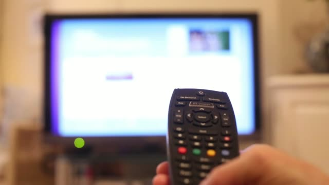 vídeos de stock e filmes b-roll de close shots a customer holds and uses a bt vision branded remote control to navigate and view bt television at home in london, uk, on thursday, may... - remote location