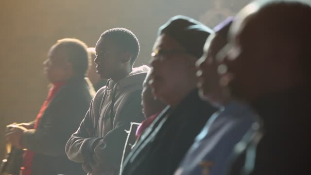 close to mid zoom out shot, the congregation pray during a sunday service at regina mundi church in soweto on june 16, 2013 in johannesburg, south... - congregation stock videos & royalty-free footage