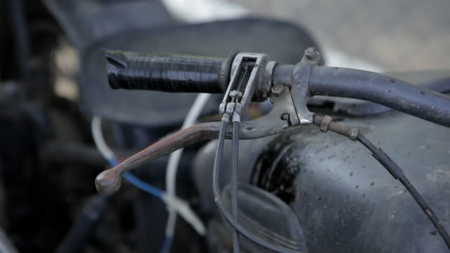 close tracking shot across the handlebars of an old motorcycle. - handlebar stock videos & royalty-free footage